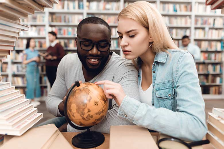 young couple play with a globe